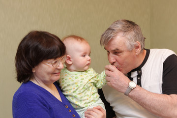 Grandfather kisses hand of baby