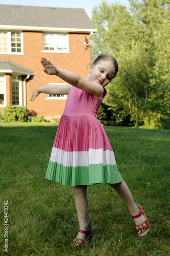 Little girl dances in the garden