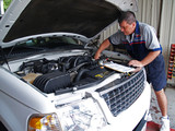 Fototapety Mechanic Performing a Routine Service Inspection