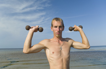 Young man with dumbbells.