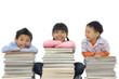 Happy schoolchildren with many books sitting