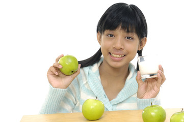 girl holding glass of milk and apple.