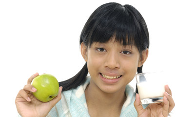 Young girl holding glass of milk and apple.