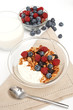 Serving of yogurt with fresh berries, muesli and milk on white b