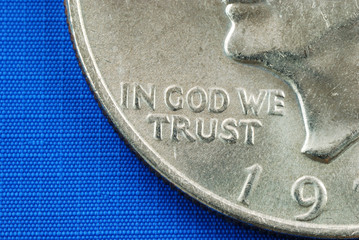 In God We Trust from the dollar coin isolated on blue