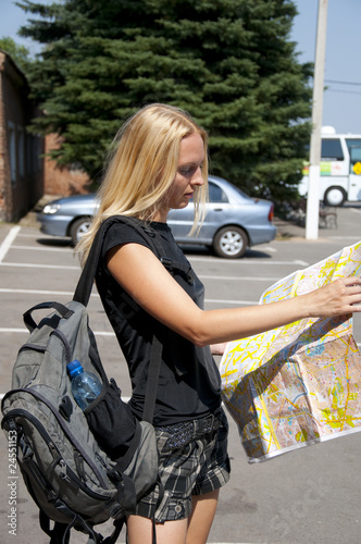 The girl-traveller with a map of the city and a backpack