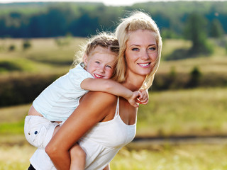 Portrait of  mother and little pretty girl outdoors
