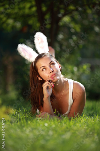 Woman with funny rabbit ears lies on a grass outdoors