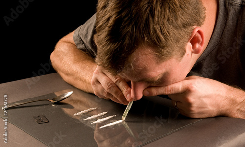 young man snorting lines of cocaine