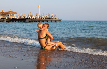 Mother and daughter hugging on the beach.