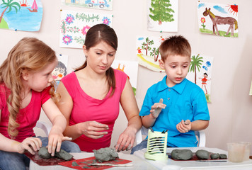 Children mould with teacher from clay.