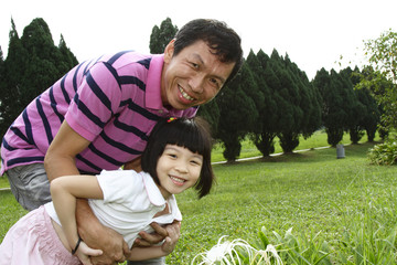 An Asian father and his daughter at a park