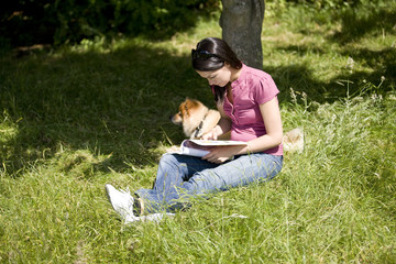 A young woman sitting with her dog, reading a magazine