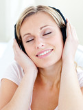 Radiant young woman listen to music wearing headphones