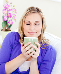 Caucasian blond woman enjoy her coffee sitting on the sofa