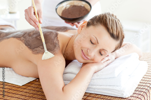 Relaxed woman enjoying a mud skin treatment