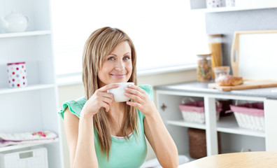 Cute young woman drinking coffee sitting in the kitchen