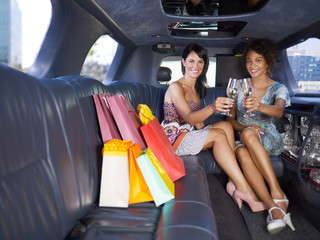 women drinking wine in limousine