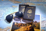 Two US American passports and sunglasses over map and brochure