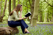 A young woman sitting on a log, reading a book