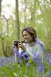 A young woman photographing bluebells, smiling