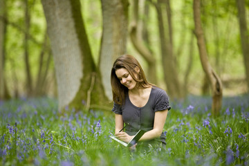 A young woman sitting amongst bluebells, drawing