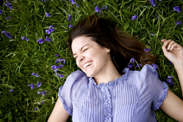 A young woman lying amongst bluebells, laughing
