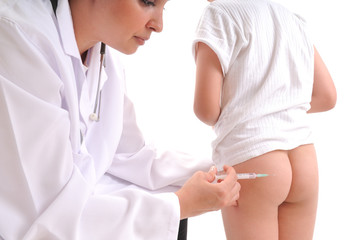 Doctor giving an injection to a little child on buttocks.
