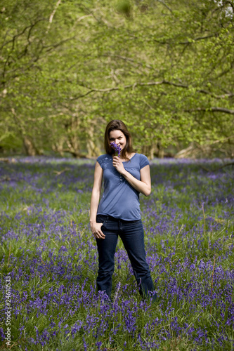 A young woman standing, holding a bunch of bluebells