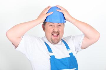Portrait d'un ouvrier grimaçant sur fond blanc