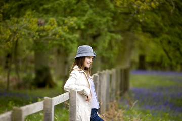A young woman leaning against a fence in the countryside