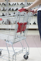Woman pushing shopping cart in store