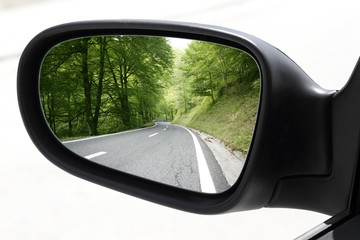 rearview car driving mirror view forest road