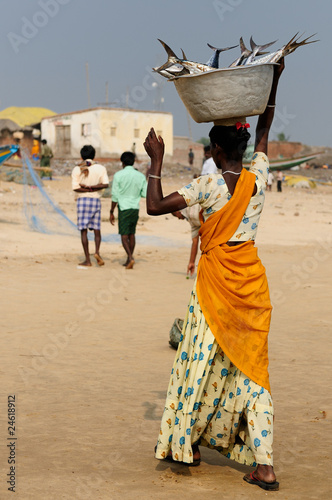 Woman with dish fish on the head on a beach, India