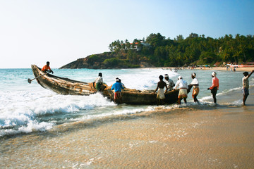 Fishermen bringing their traditional boat to the sea