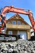 Hausbau: fertiges Haus mit Bagger