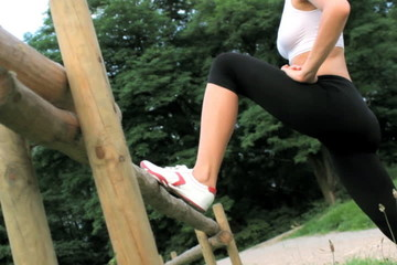 Woman stretching legs outdoors, dolly shot