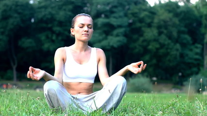 Woman sitting on the grass in park and meditating, dolly shot