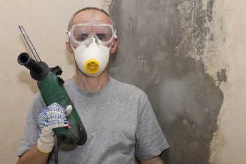 man in respirator with screwdriver