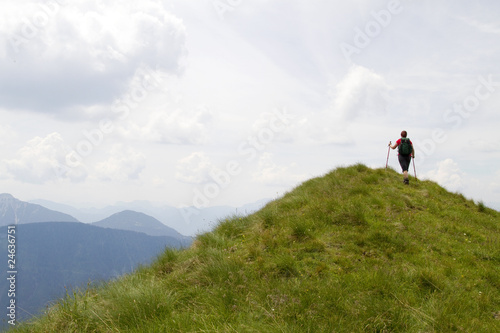 Hiker climbing up a green mountain
