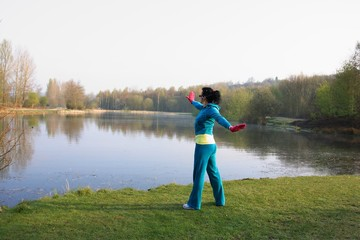 Woman exercising on a lakeside with her MP3 headset