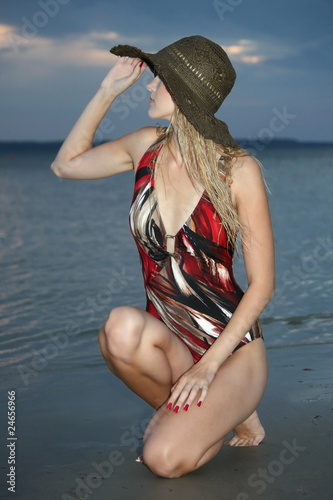 blond woman sitting on the beach