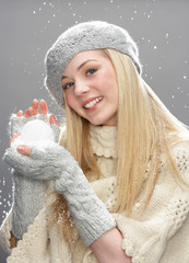 Teenage Girl Wearing Warm Winter Clothes And Hat Holding Snowbal
