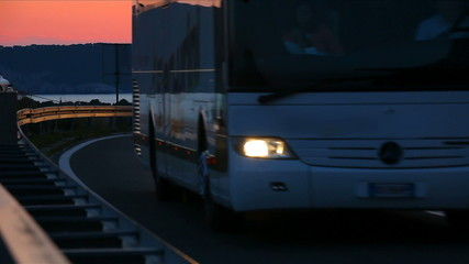 Car and buss driving in sunset