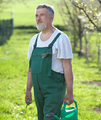 Portrait of a senior man gardening in his garden