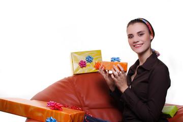 nette Frau mit Geschenken im Sessel