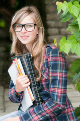 Student with notebooks in the campus park