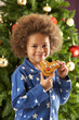 Young Boy Eating Cookie In Front Of Christmas Tree