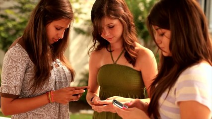 Three pretty teenage girls stop texting and smile.