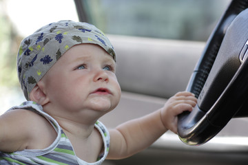 Funny baby holds a wheel in car